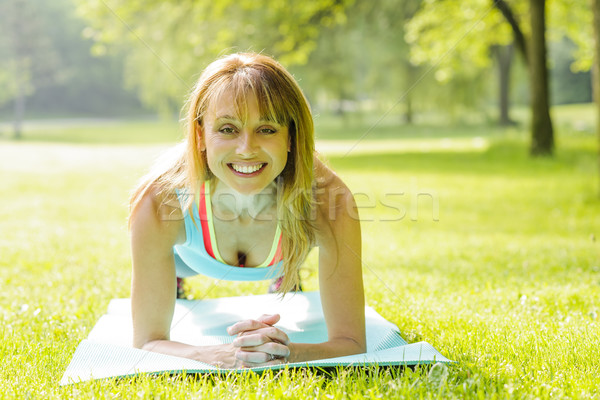 Woman holding plank pose outside Stock photo © elenaphoto
