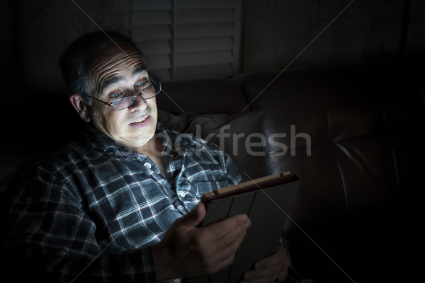Man reading tablet at night Stock photo © elenaphoto