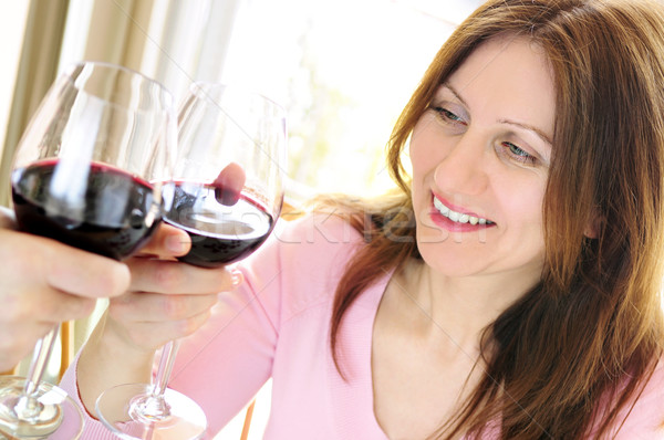 Mature woman toasting with red wine Stock photo © elenaphoto
