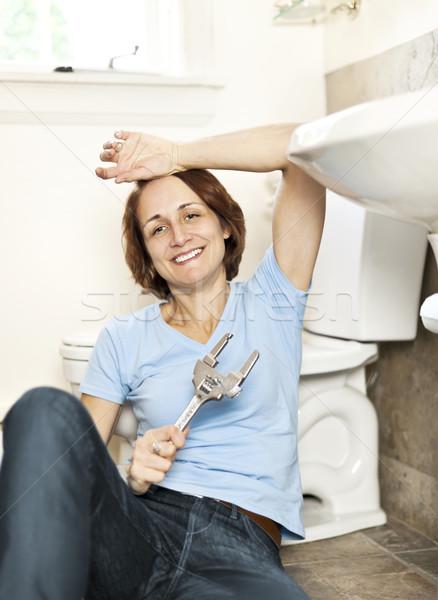 Woman fixing plumbing Stock photo © elenaphoto