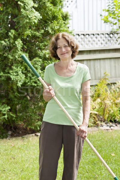 Senior woman holding rake Stock photo © elenaphoto