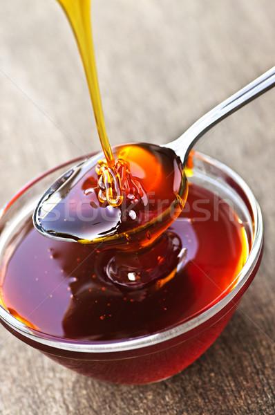 Honey dripping onto spoon Stock photo © elenaphoto