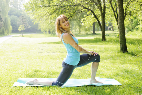 Smiling woman stretching in park Stock photo © elenaphoto