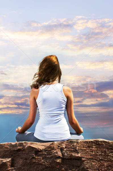 Young girl meditating at sunset Stock photo © elenaphoto