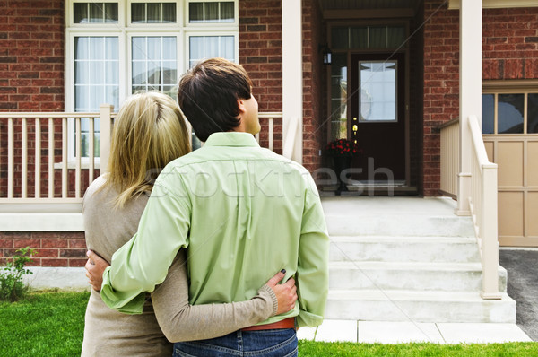 Happy couple in front of home Stock photo © elenaphoto