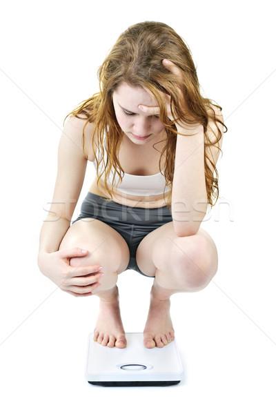 Young girl on bathroom scale looking upset Stock photo © elenaphoto