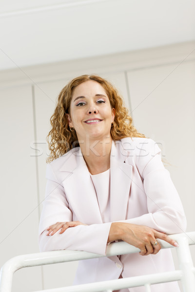 Happy businesswoman standing in hallway Stock photo © elenaphoto