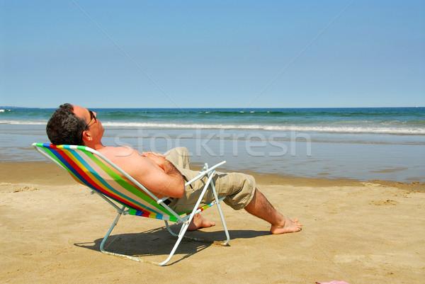 Férfi megnyugtató tengerpart napozószék óceán part Stock fotó © elenaphoto