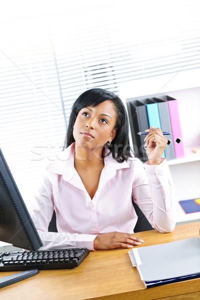 Black businesswoman working at desk Stock photo © elenaphoto
