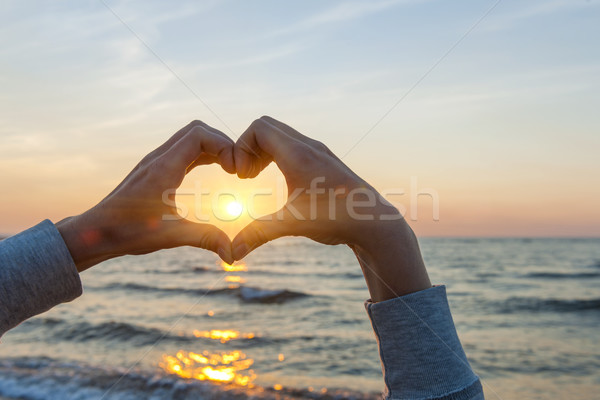 Hands in heart shape framing sun Stock photo © elenaphoto