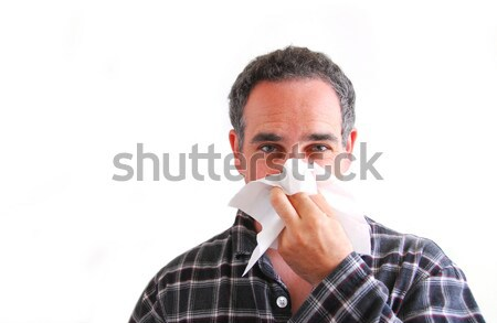 Man with cold blowing nose Stock photo © elenaphoto