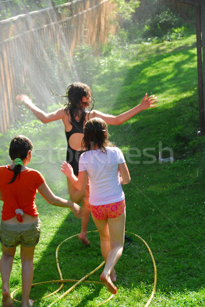 Girls run sprinkler Stock photo © elenaphoto