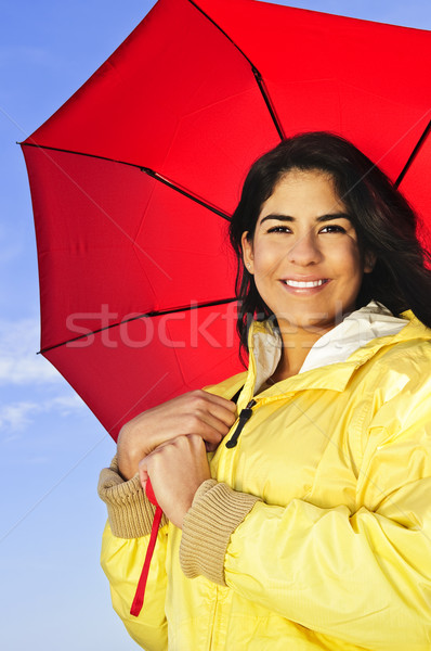 Beautiful young woman in raincoat with umbrella Stock photo © elenaphoto