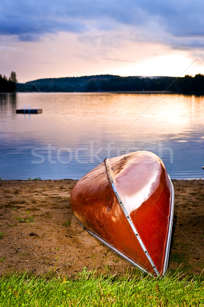 Lake sunset with canoe on beach Stock photo © elenaphoto