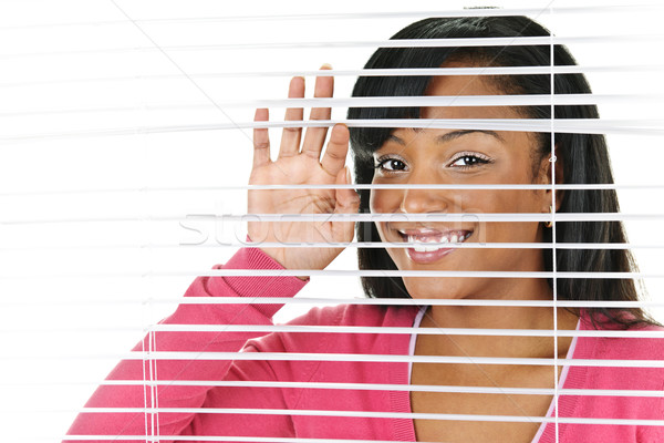 Smiling woman looking through blinds Stock photo © elenaphoto