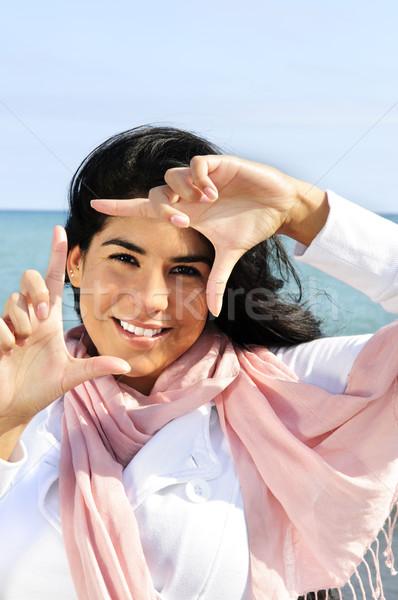 Beautiful young woman framing her face Stock photo © elenaphoto