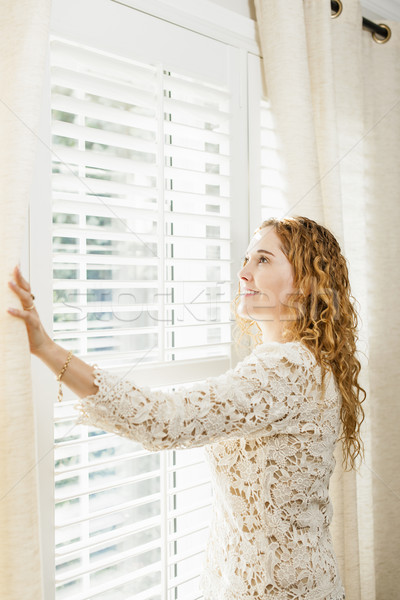 Smiling woman looking out window Stock photo © elenaphoto