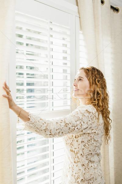 Gülümseyen kadın bakıyor dışarı pencere mutlu kadın Stok fotoğraf © elenaphoto