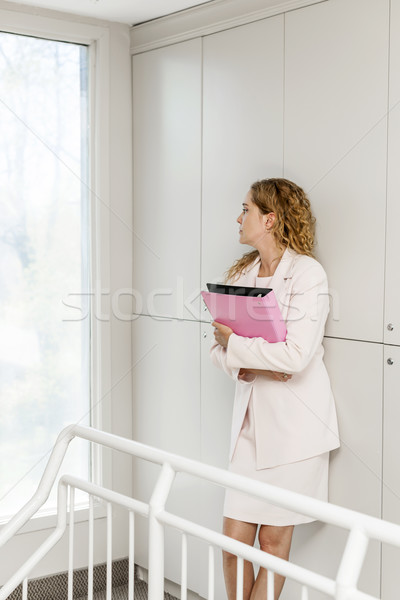 Businesswoman standing in hallway thinking Stock photo © elenaphoto