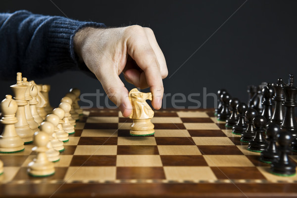 Stock photo: Hand moving knight on chess board