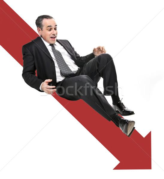 Businessman sliding down red arrow Stock photo © elenaphoto
