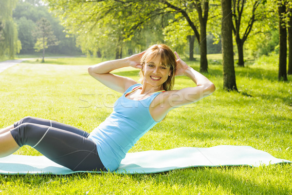 Woman doing situps in park Stock photo © elenaphoto