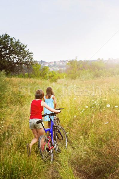 Girls walking bicycles in field Stock photo © elenaphoto