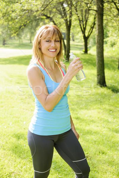 Active woman holding water bottle outside Stock photo © elenaphoto