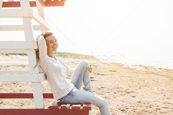 Young woman sitting on beach lifeguard chair Stock photo © elenaphoto