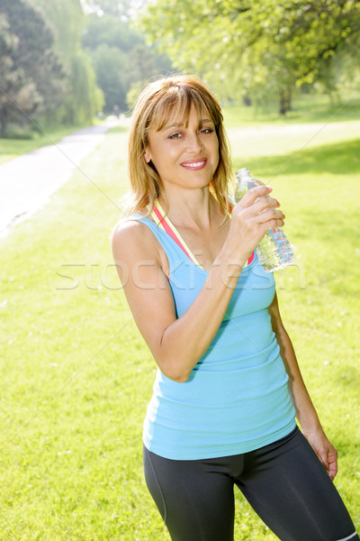 Happy woman drinking water while working out Stock photo © elenaphoto