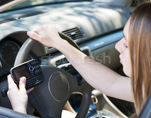 Teenage girl texting and driving Stock photo © elenaphoto
