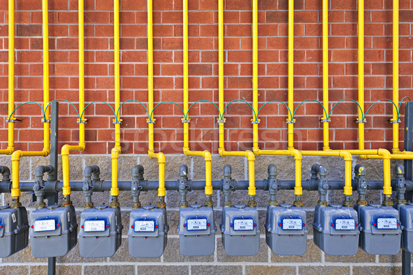 Alto parede de tijolos amarelo pipes Foto stock © elenaphoto