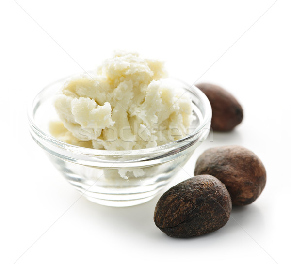 Shea butter and nuts in bowl Stock photo © elenaphoto