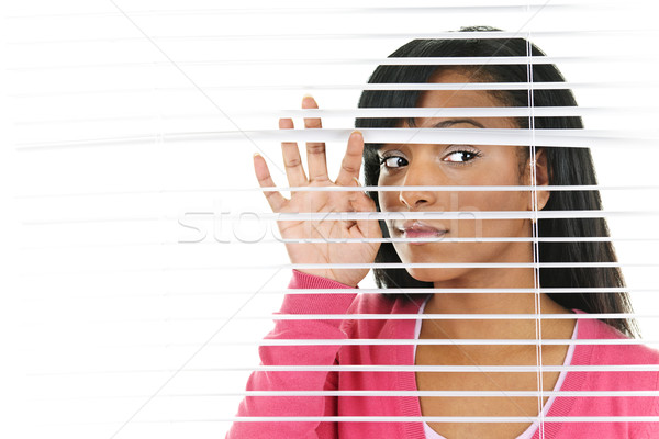 Woman looking through venetian blinds Stock photo © elenaphoto