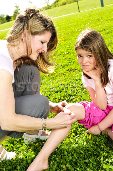 Mother putting bandage on child Stock photo © elenaphoto