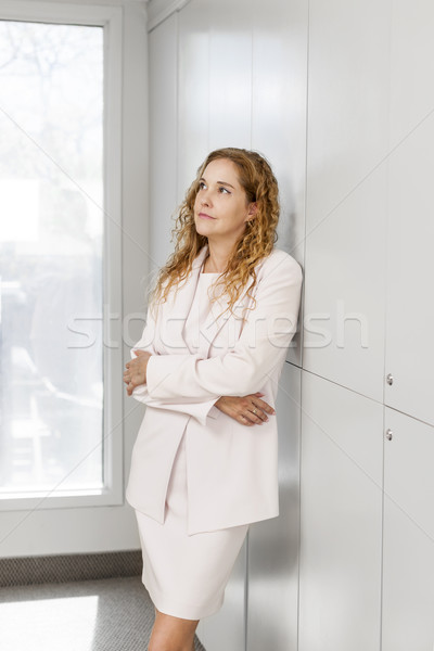 Thinking businesswoman standing in hallway Stock photo © elenaphoto