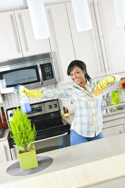 Mulher jovem limpeza cozinha sorridente jovem mulher negra Foto stock © elenaphoto