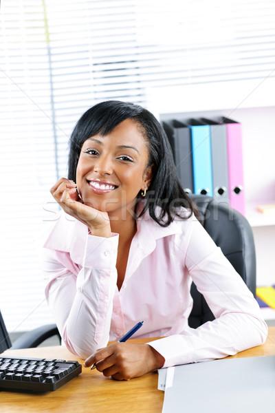 Black businesswoman at desk in office Stock photo © elenaphoto