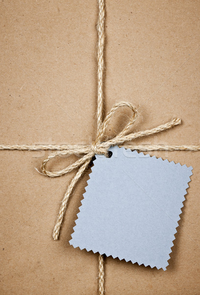 Gift with blue card in brown paper Stock photo © elenaphoto