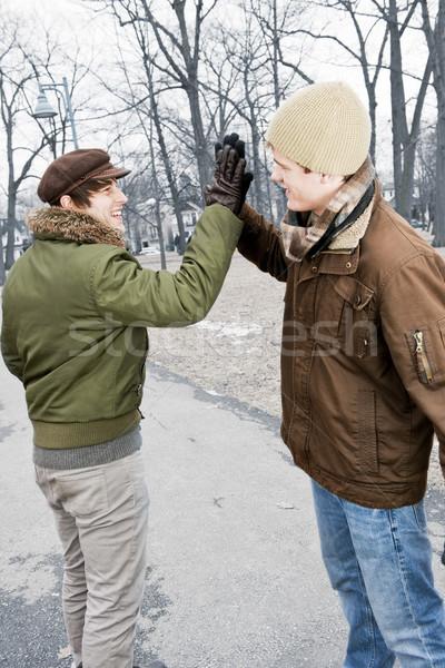 Two men doing high five in park Stock photo © elenaphoto