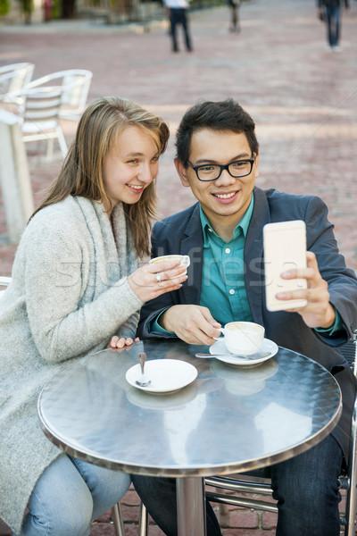 Młodych ludzi telefonu komórkowego Kafejka dwa uśmiechnięty patrząc Zdjęcia stock © elenaphoto