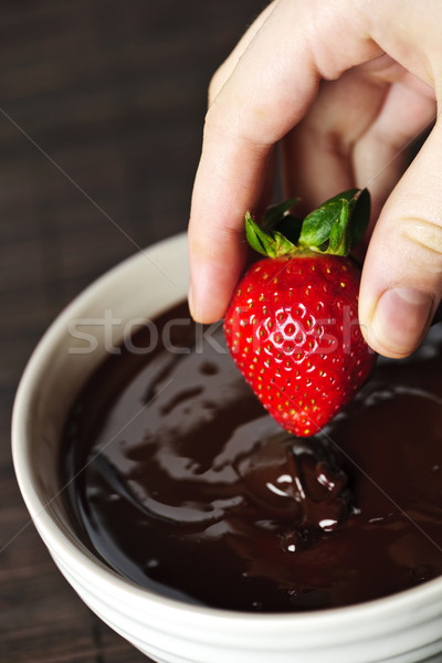 Hand dipping strawberry in chocolate Stock photo © elenaphoto