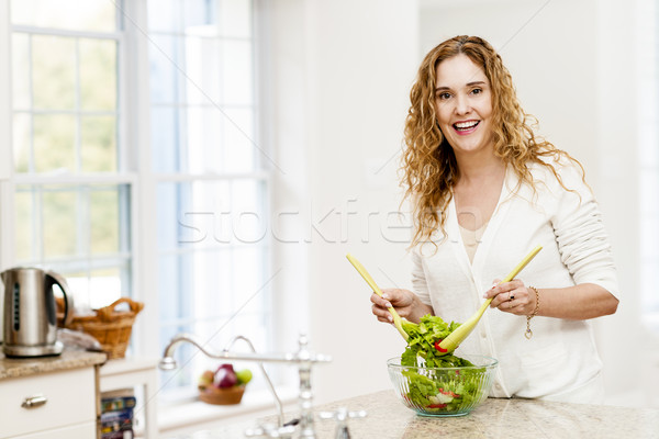 Smiling woman tossing salad in kitchen Stock photo © elenaphoto