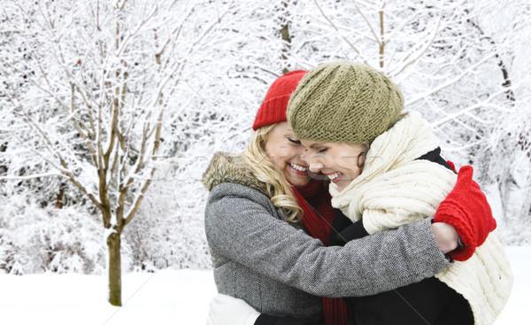 Two girl friends hugging outside in winter Stock photo © elenaphoto
