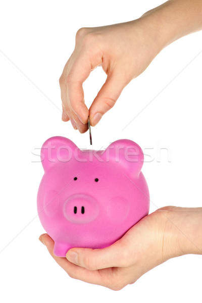 Hand putting coin in piggy bank Stock photo © elenaphoto