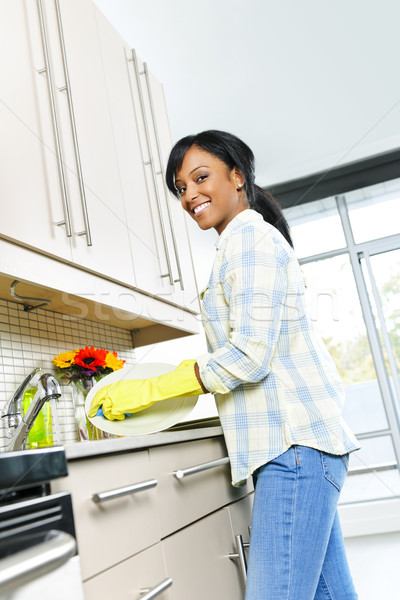 Happy young woman washing dishes Stock photo © elenaphoto