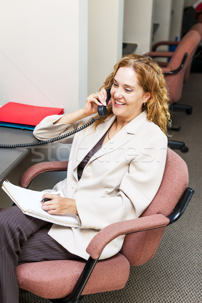 Smiling woman on telephone at office desk Stock photo © elenaphoto