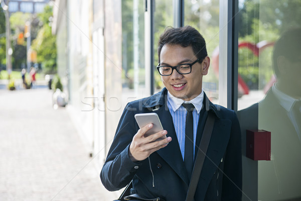 Young asian man looking at mobile phone Stock photo © elenaphoto