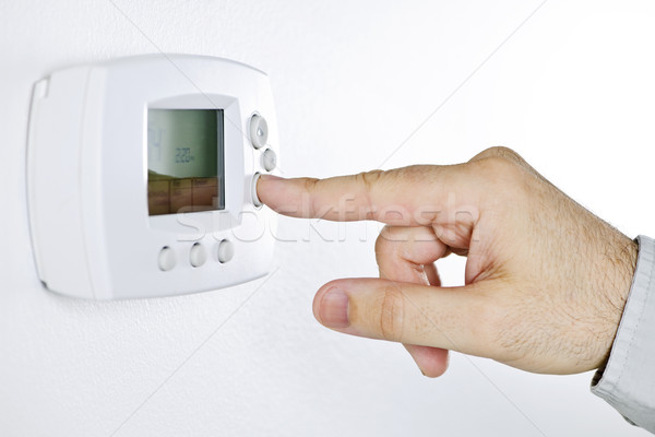 Hand setting digital thermostat Stock photo © elenaphoto