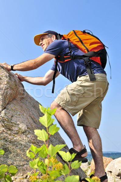 Homem escalada mochila rocha feliz Foto stock © elenaphoto